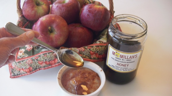 drizzling amber honey on homemade applesauce