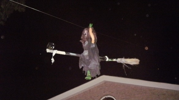 witch on broomstick in the air at neighbour's house decorated for halloween