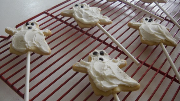dairy, egg and peanut/tree nut free ghost cookies on a stick iced with dairy free vanilla icing and enjoy life chocolate chips