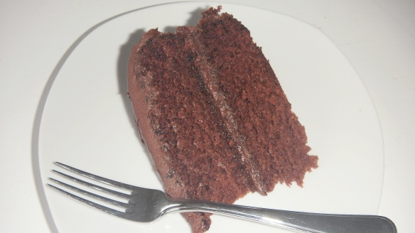 slice of dairy and egg free chocolate birthday cake on a plate with fork
