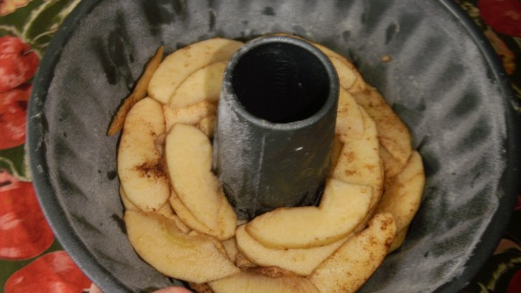 sliced cinnamon apples over caramel in bundt pan