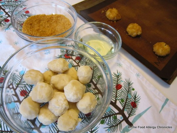 dairy, egg and peanut/tree nut free thumbprint cookie dough rolled into balls, canola oil, and corn flake crumbs in a bowl