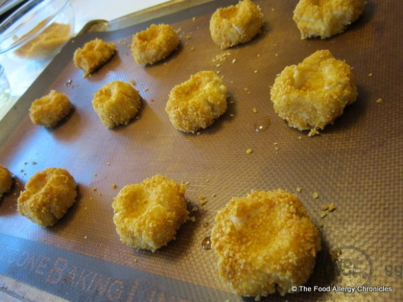 dairy, egg and peanut/tree nut free thumbprint cookie dough balls on a cookie sheet with a pressed indent