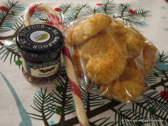 a package of dairy, egg and peanut/tree nut free thumbprint cookies with a candy cane and a small jar of strawberry jam