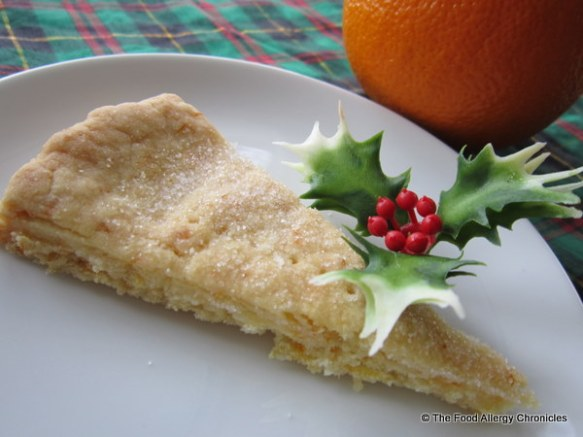 a slice of dairy and peanut/tree nut free orange shortbread on a plate