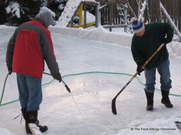 my brother and andy watering the backyard rink, ottawa, 2011