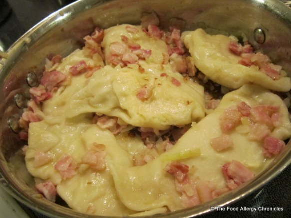 dairy free daiya pierogies frying in a pan with diced bacon and onion