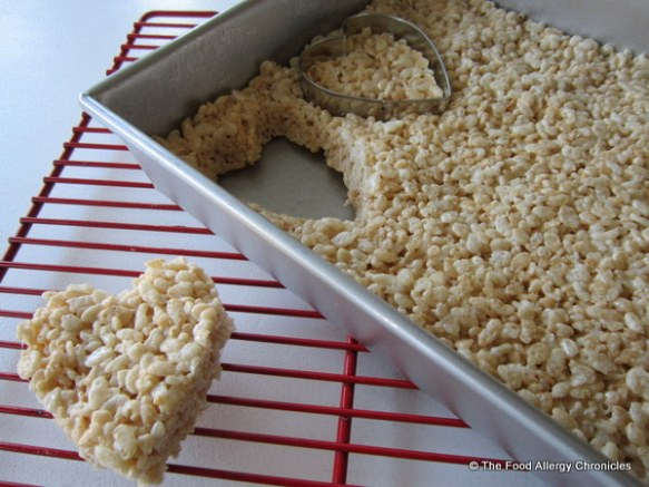 Dairy free rice krispie treats being cut into hearts with cookie cutter
