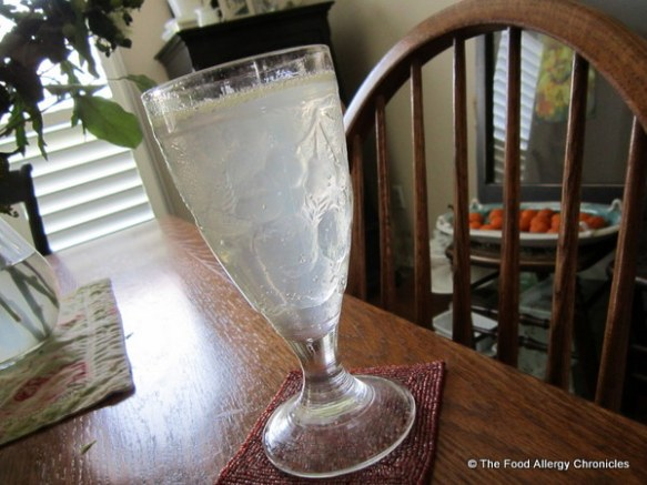 A glass of sparkling water and fresh lemon juice