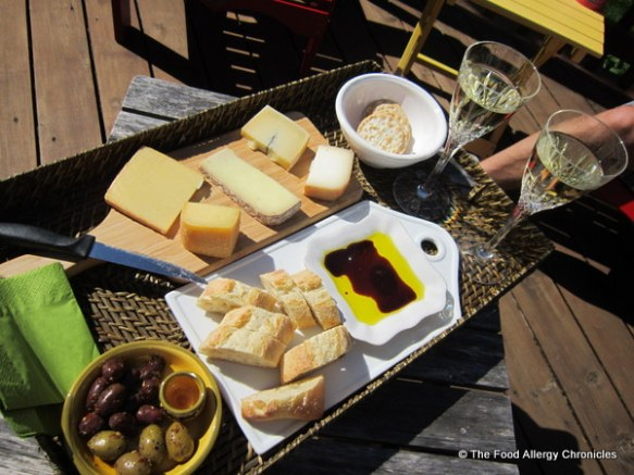 A tray of cheeses, extra virgin olive oil and balsamic vinegar from Cheese Secrets, bread, olives and white wine