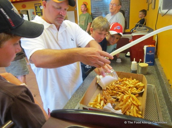 Adding salt and vinegar to Albert's plates of fries