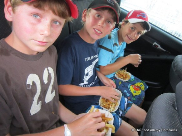 The boys enjoying their plates of Albert's fries in the car