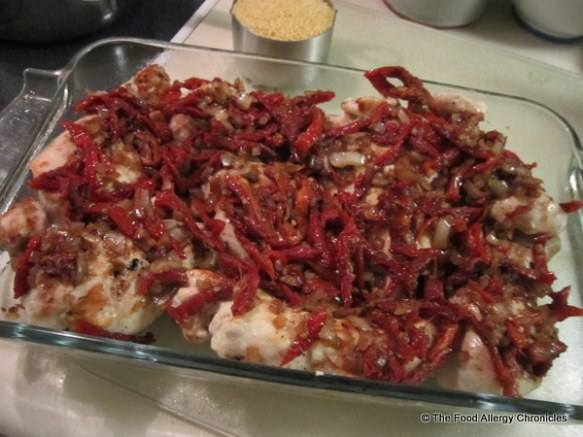 Barbecued chicken breasts with sun-dried tomato topping ready for the oven