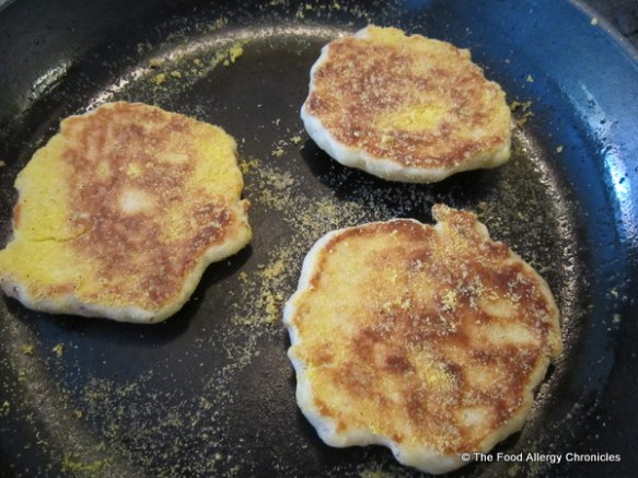 Dairy, Egg, Soy and Peanut/Tree Nut Free English Muffins cooking in a cast iron pan.