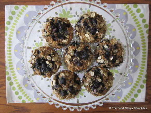 A glass cake plate serving Dairy, Egg, Soy and Peanut/Tree Nut Free Oatmeal Blueberry Muffins