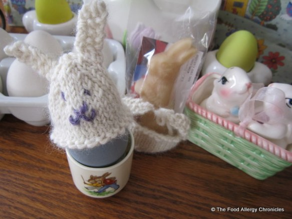 A knitted Bunny Egg Cozy a top of a 'grape juice' dyed Eggnot