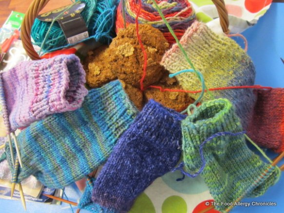 A basket of Dairy, Egg, Soy and Peanut/Tree Nut Free Date Bran Whole-wheat Muffins surrounded by the unfiinished socks the lovely ladies at knitting are working on